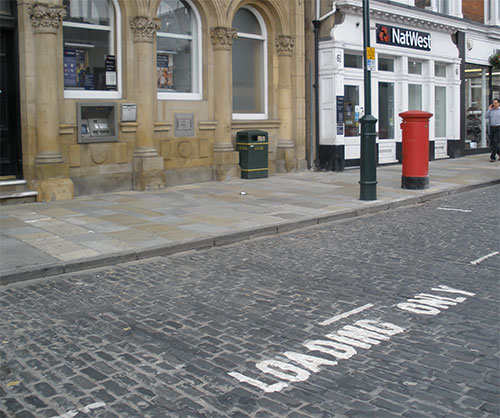 Loading bays denoted by words 'Loading Only' written on road accompanied by dashed lines around loading space